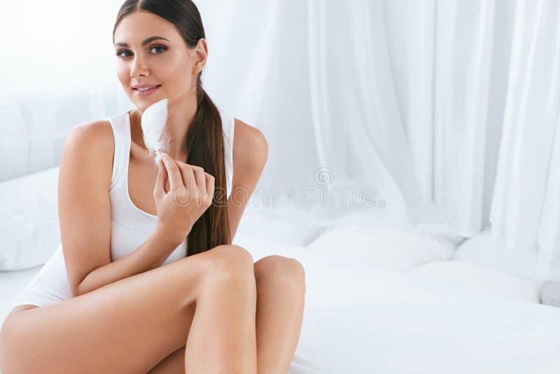 Härlig kvinna med skönhetframsidan som trycker på mjuk hud med fjädern royaltyfri foto
