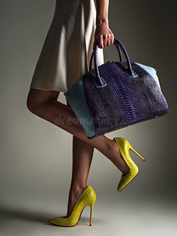 Härlig kvinna med slanka ben i gula höga häl Den trendiga flickan rymmer den stilfulla blåa påsen royaltyfri bild