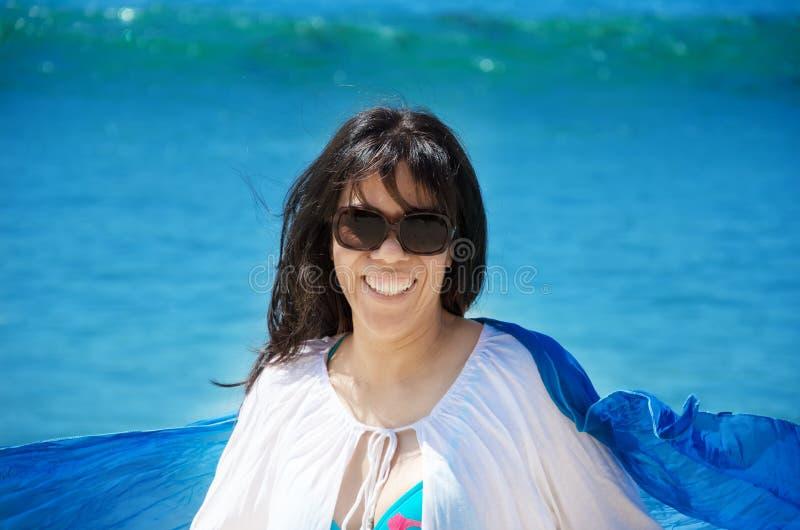 Härlig kvinna med snäckskalet på stranden royaltyfri bild