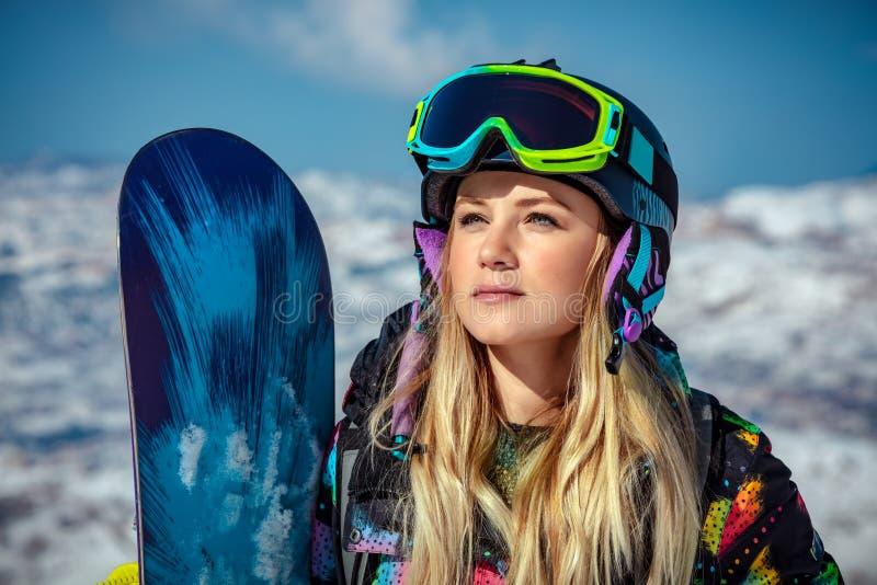 Härlig kvinna med snowboarden arkivbild