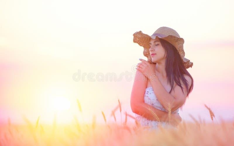 Härlig kvinna med sommarhatten i vetefält på solnedgången arkivbild