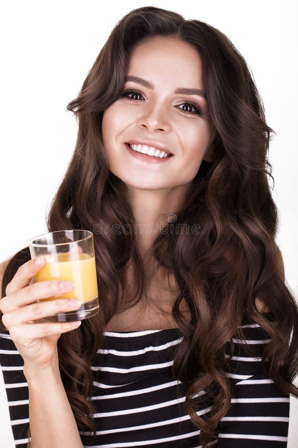 Härlig kvinna med sund hud, hårkrullning och orange fruktsaft som poserar i studio Härlig le flicka royaltyfri bild