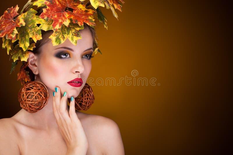 Härlig kvinna med trädautmnprydnaden i huvud arkivfoto