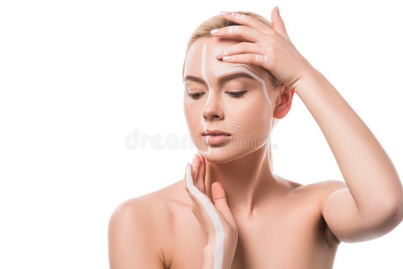 härlig kvinna med vita linjer på framsidan som trycker på huvudet med händer arkivfoto