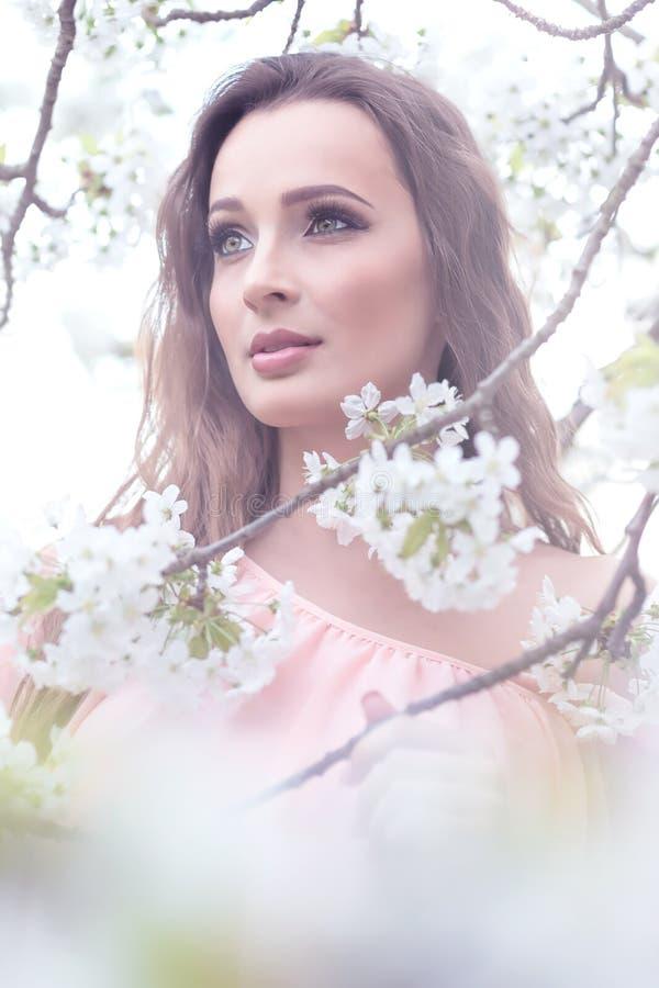 Härlig kvinna - nära blomningträden arkivbilder