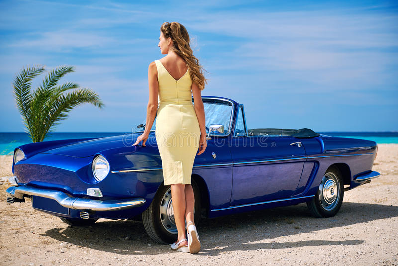 Härlig kvinna nära den retro cabrioletbilen royaltyfri bild