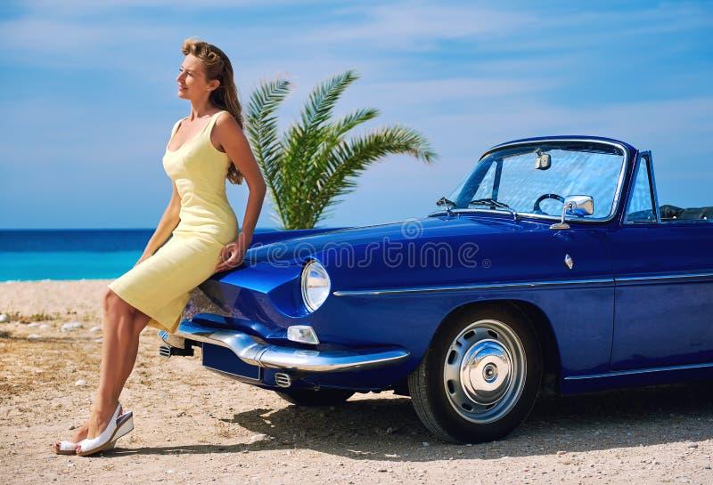 Härlig kvinna nära den retro cabrioletbilen arkivfoton