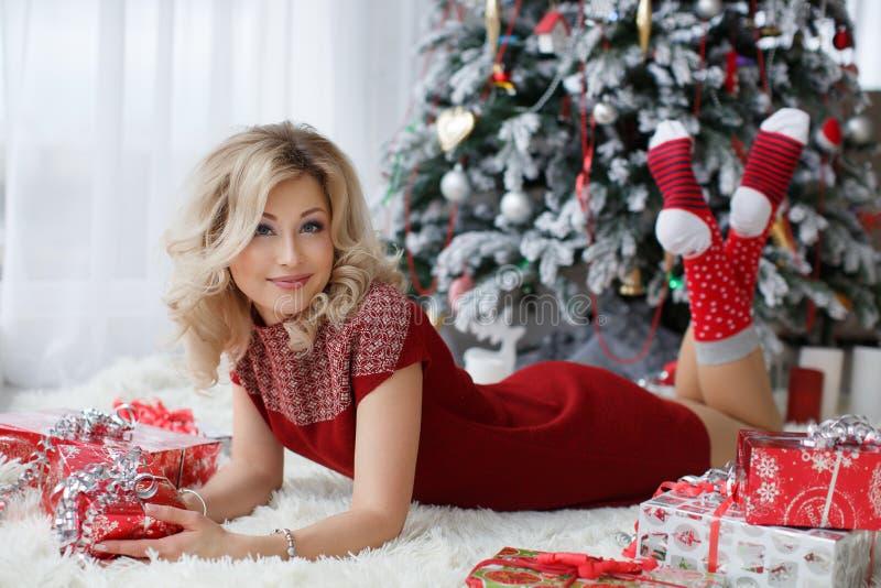 Härlig kvinna nära en julgran med en kopp kaffe med marshmallower royaltyfri fotografi