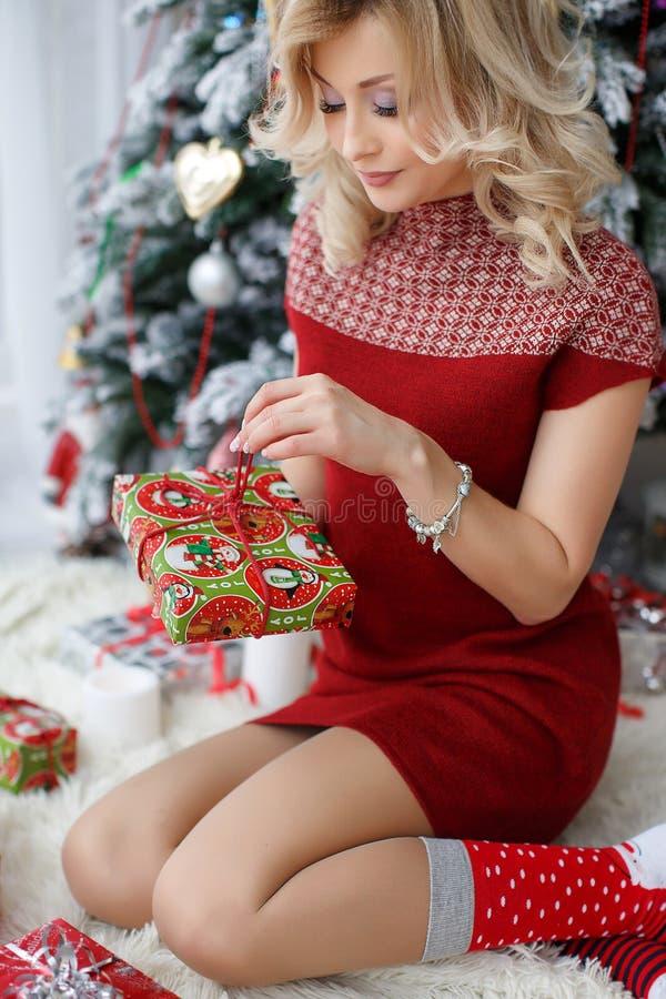 Härlig kvinna nära en julgran med en kopp kaffe med marshmallower arkivbild