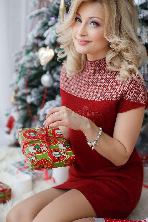 Härlig kvinna nära en julgran med en kopp kaffe med marshmallower royaltyfria foton