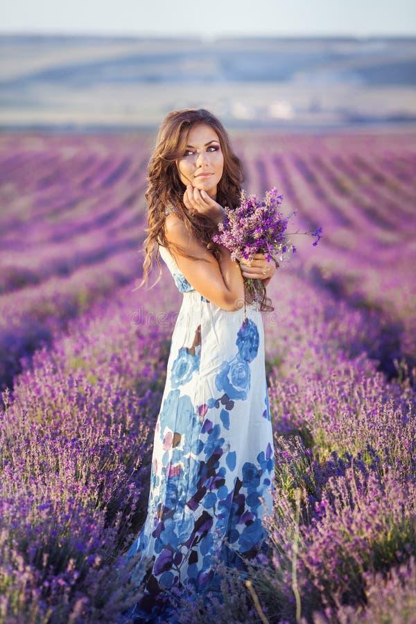 Härlig kvinna och ett lavendelfält royaltyfri foto