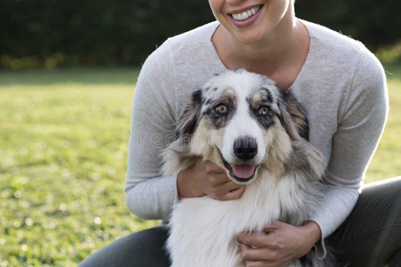 Härlig kvinna och hennes hund som tillsammans poserar arkivbilder