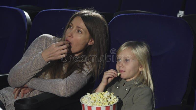 Härlig kvinna och hennes liten dotter som äter hållande ögonen på film för popcorn på bion royaltyfria bilder