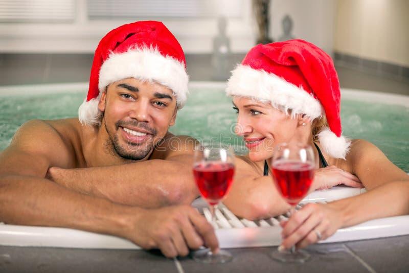Härlig kvinna och man med den santa hatten som kopplar av i bubbelpool på sp royaltyfria bilder
