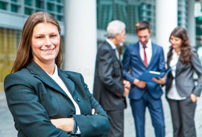 Härlig kvinna på bakgrunden av affärsfolk arkivfoto