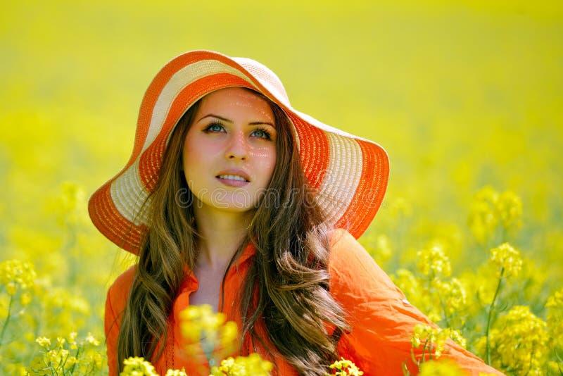 Härlig kvinna på blommande rapsfröfält i sommar arkivbild