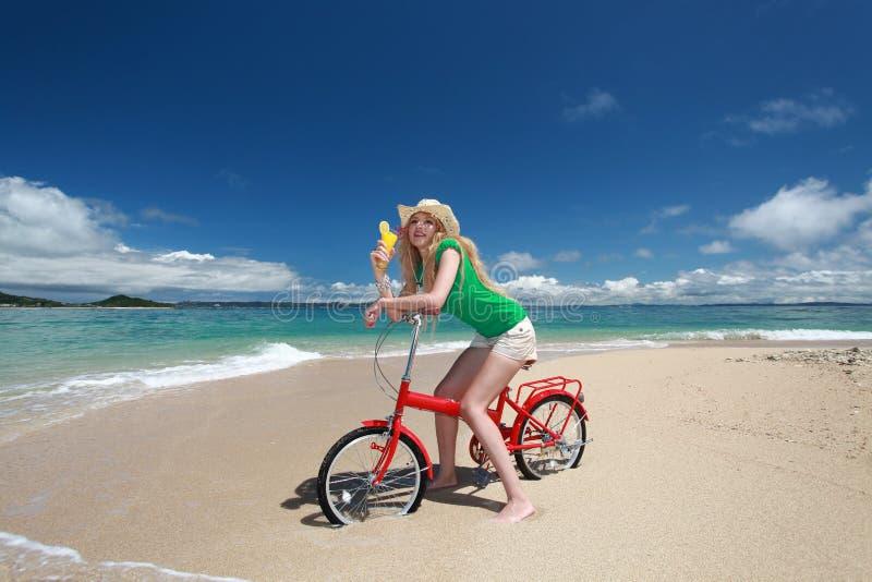 Härlig kvinna på cykeln på stranden fotografering för bildbyråer