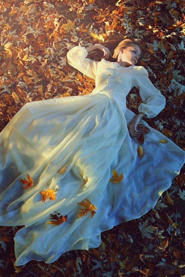 Härlig kvinna på en säng av sidor arkivfoto
