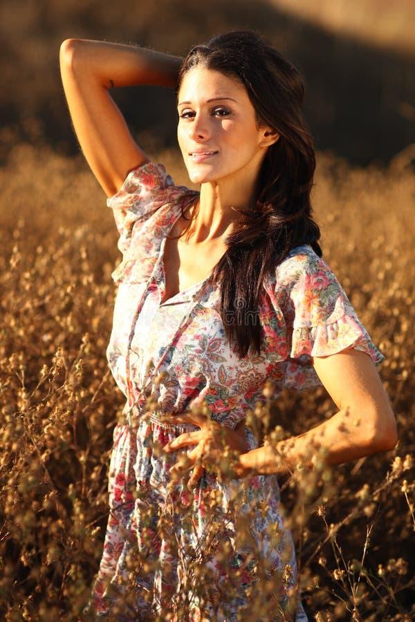 Härlig kvinna på ett fält i sommartid arkivfoton