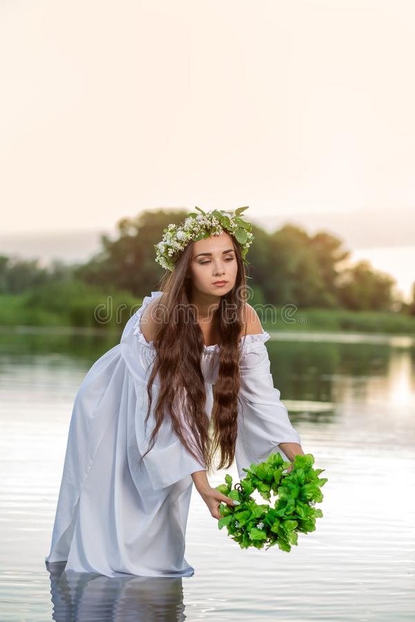Härlig kvinna på flodbanken Lantlig kvinna med en krans i en genomskinlig klänning arkivbild