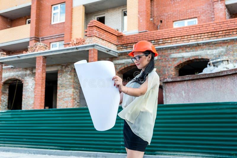 Härlig kvinna på konstruktionsplatsen som ser ritningen royaltyfri foto