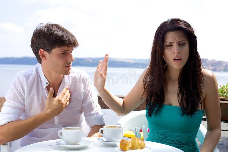 Härlig kvinna som är ilsken med pojkvännen som inte är villig att lyssna arkivfoto