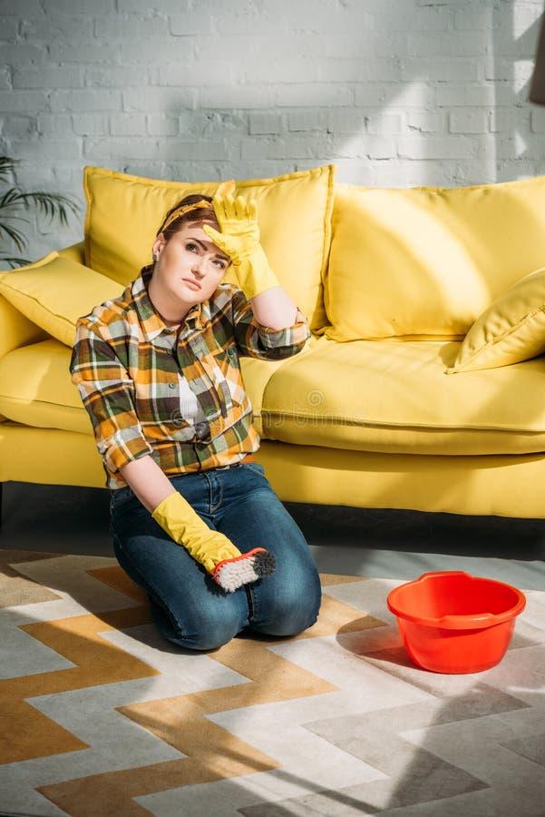 härlig kvinna som är trött, når att ha gjort ren matta royaltyfri bild