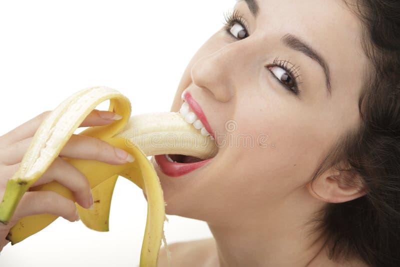 Härlig kvinna som äter bananen fotografering för bildbyråer