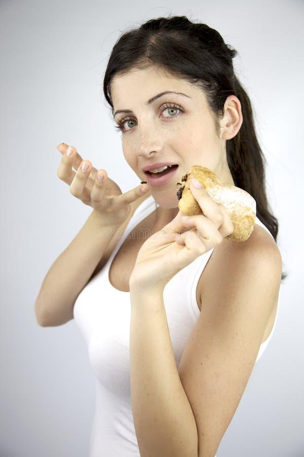 Härlig kvinna som äter det hållande mellanmålet för chipchoklad royaltyfri foto