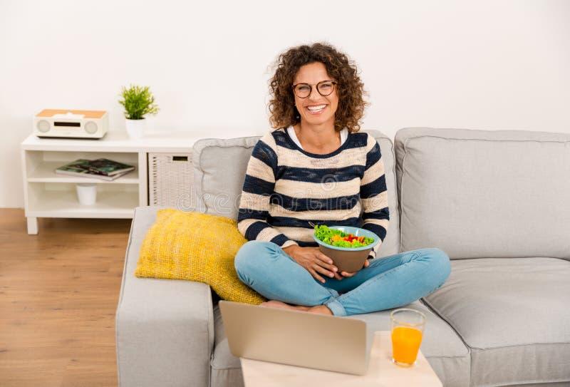 Härlig kvinna som äter en sallad arkivbild