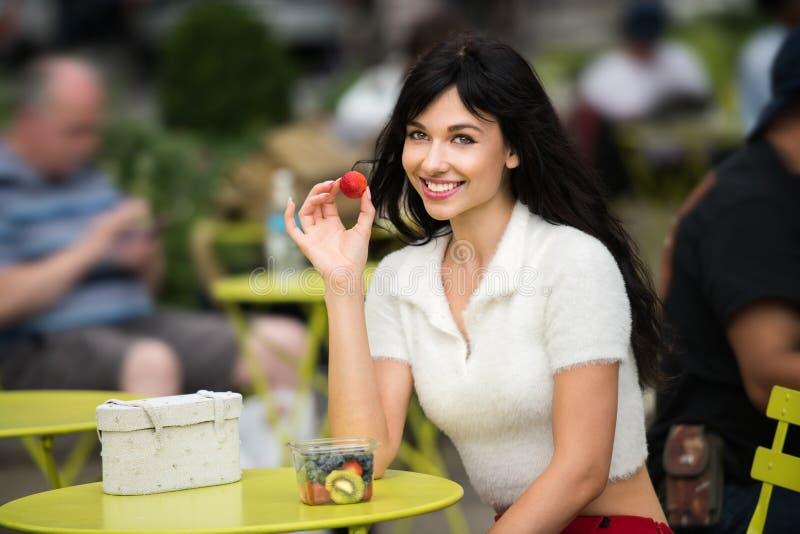 Härlig kvinna som äter fruktlunch ut ur kontor på stadsgatan på offentligt ställe royaltyfri bild