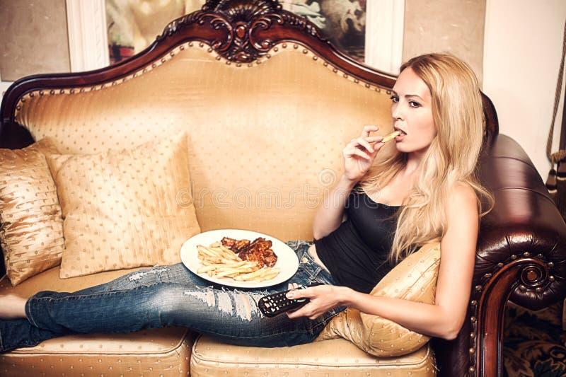 Härlig kvinna som äter potatisen och håller ögonen på TV royaltyfria foton