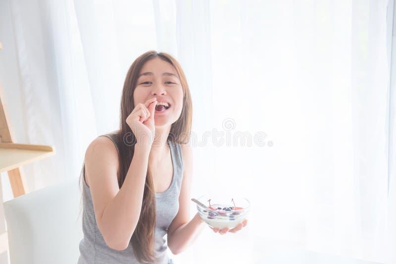 Härlig kvinna som äter yoghurt med bär för frukost arkivfoton