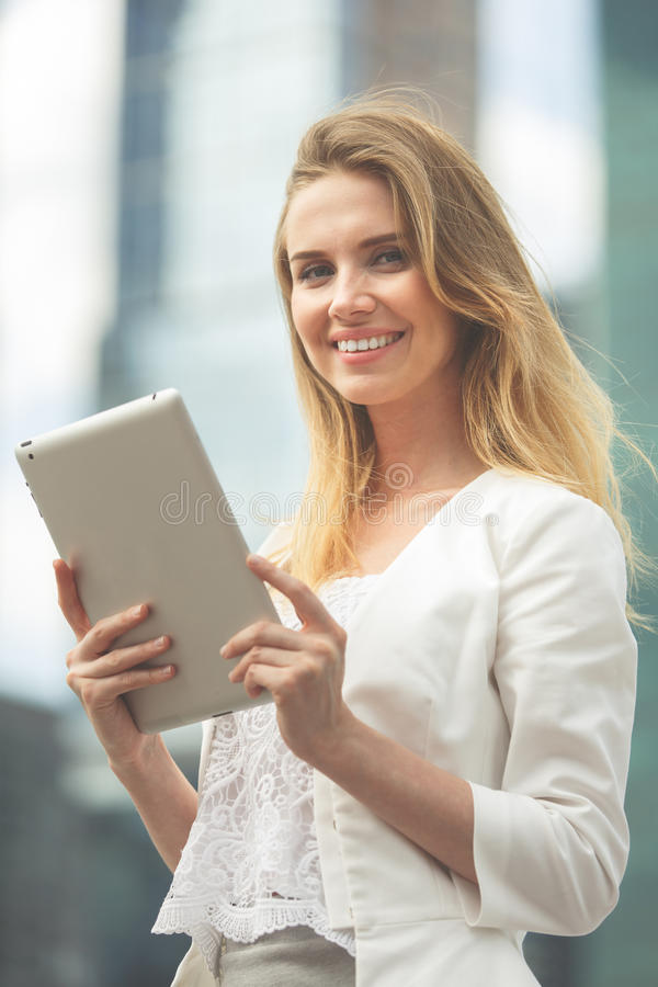 Härlig kvinna som använder den elektroniska fliken i gatan royaltyfri foto
