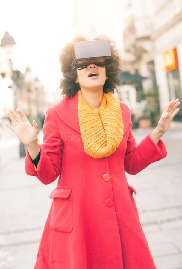 Härlig kvinna som använder tekniskt avancerade utomhus- virtuell verklighetexponeringsglas royaltyfria foton