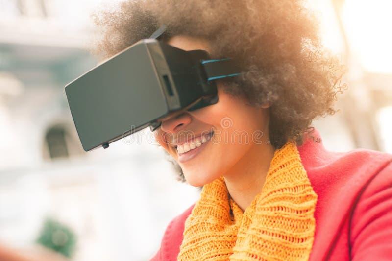 Härlig kvinna som använder tekniskt avancerade utomhus- virtuell verklighetexponeringsglas fotografering för bildbyråer