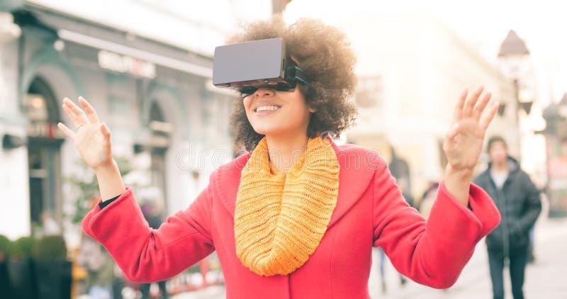 Härlig kvinna som använder tekniskt avancerade utomhus- virtuell verklighetexponeringsglas royaltyfri foto