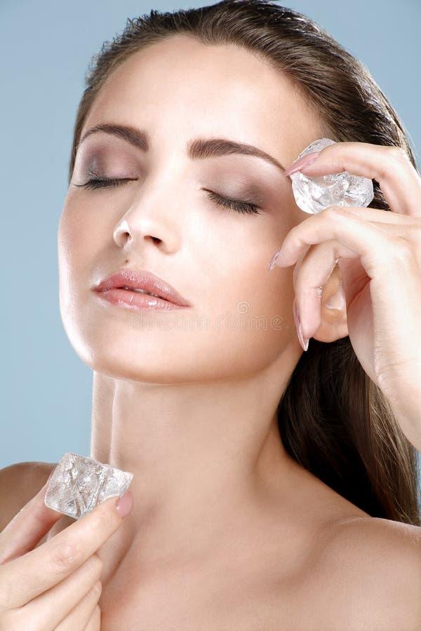 Härlig kvinna som applicerar behandling för iskub på framsida royaltyfria foton