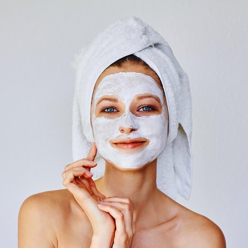 Härlig kvinna som applicerar den ansikts- maskeringen på hennes framsida Hudomsorg och behandling, brunnsort, naturlig sk?nhet oc royaltyfria bilder
