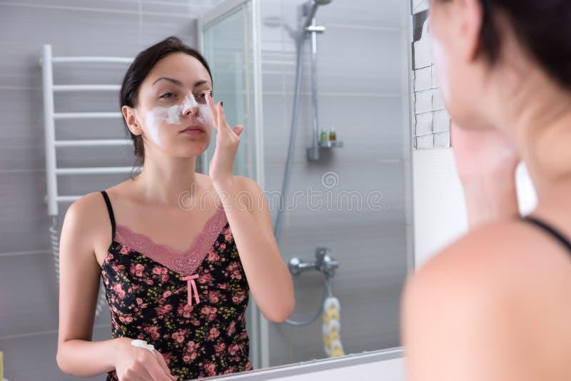 Härlig kvinna som applicerar den naturliga ansikts- maskeringen i badrummet royaltyfria bilder