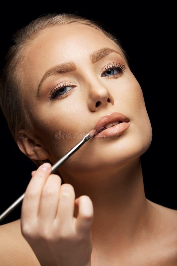Härlig kvinna som applicerar läppstift fotografering för bildbyråer