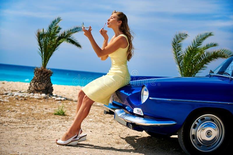 Härlig kvinna som applicerar läppstift nära den retro bilen royaltyfria bilder