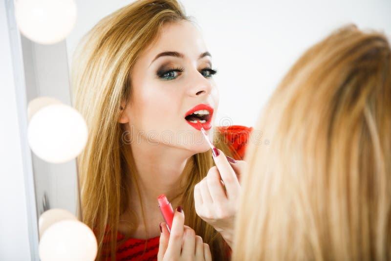 Härlig kvinna som applicerar läppstift på spegeln royaltyfri foto