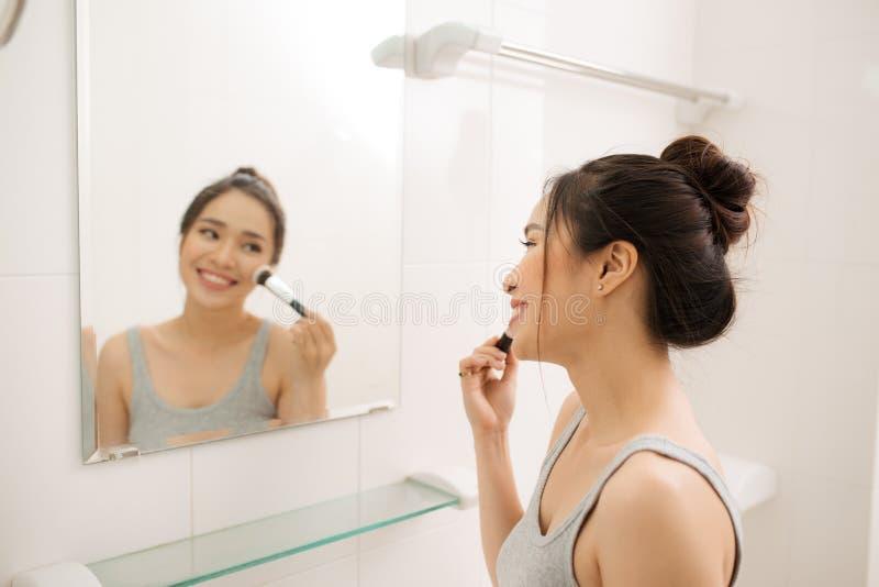 Härlig kvinna som applicerar makeuprouge i hennes badrum arkivfoton