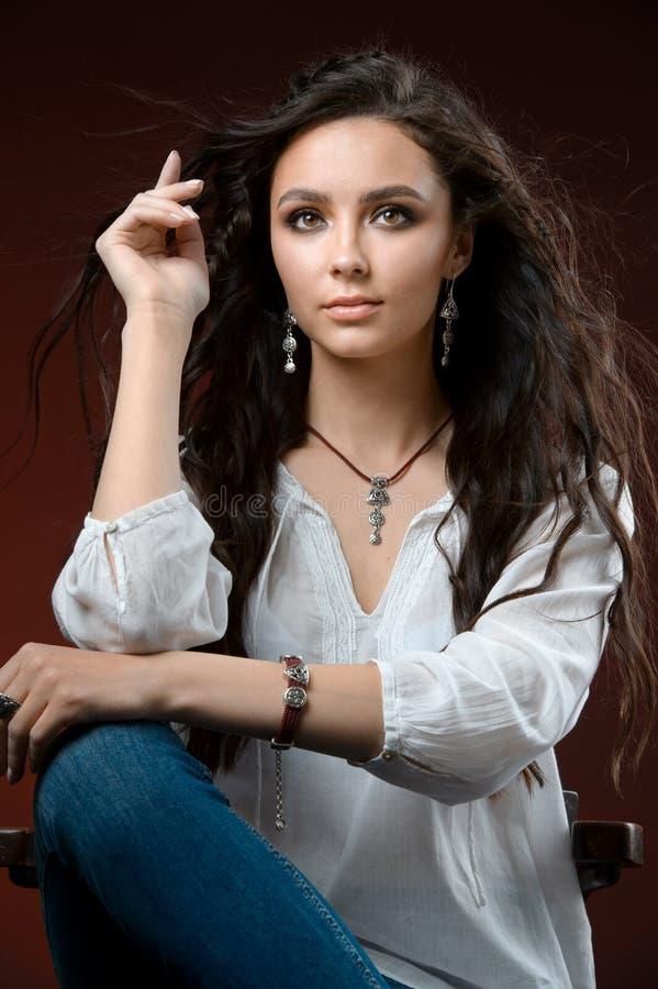 Härlig kvinna som av visar hennes smycken i bärande tillbehör och smycken för modebegrepp som isoleras på en vit bakgrund arkivfoto