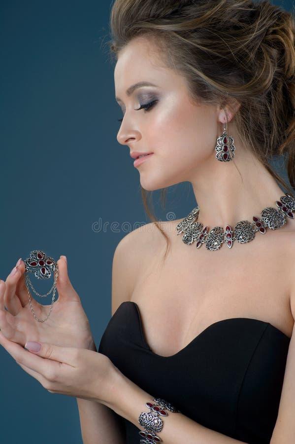 Härlig kvinna som av visar hennes smycken i modebegreppskläder arkivbilder
