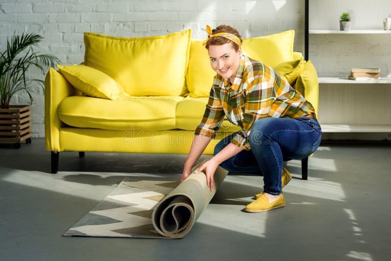 härlig kvinna som avlägsnar matta för rengörande golv royaltyfri foto
