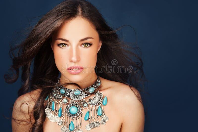 Härlig kvinna som bär den stora glamorösa halsbandet royaltyfri bild