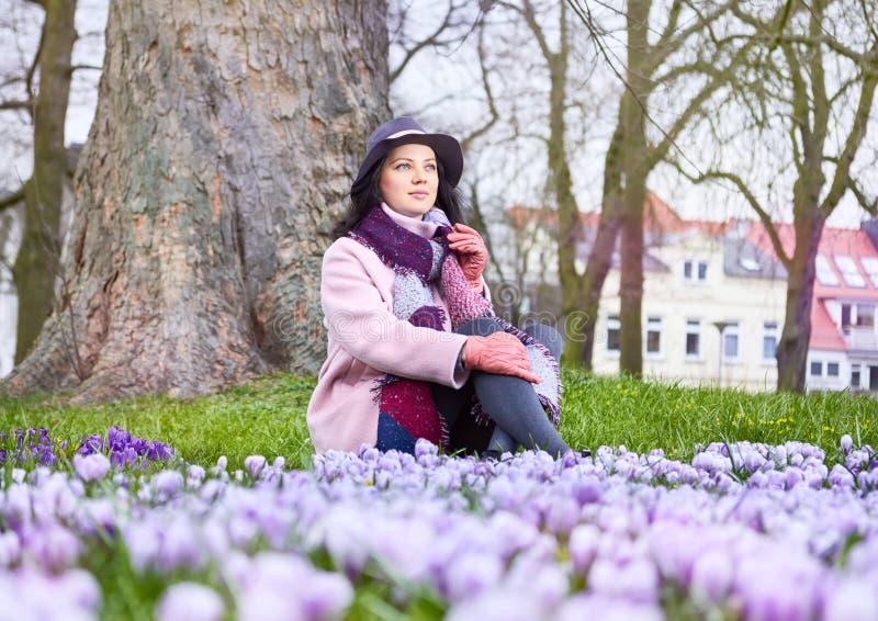 Härlig kvinna som bär med vårblommor royaltyfria bilder
