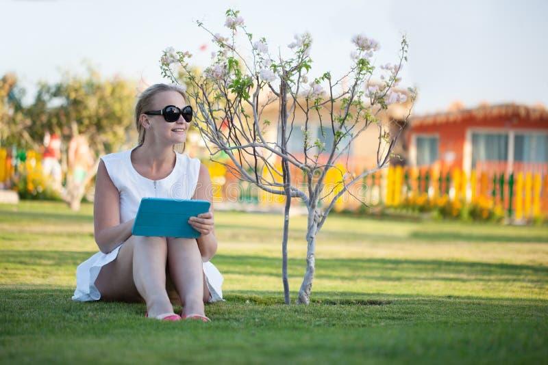 Härlig kvinna som barfota sitter på en gräsmatta royaltyfri foto
